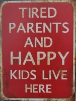 """Tekstbord:""""Tired parents and happy kids live here"""""""