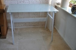 Bureau  met  metalen  poten  en  glazen  blad.