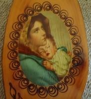 Bronskleurig kruisbeeld en religieuze afbeelding op hout.